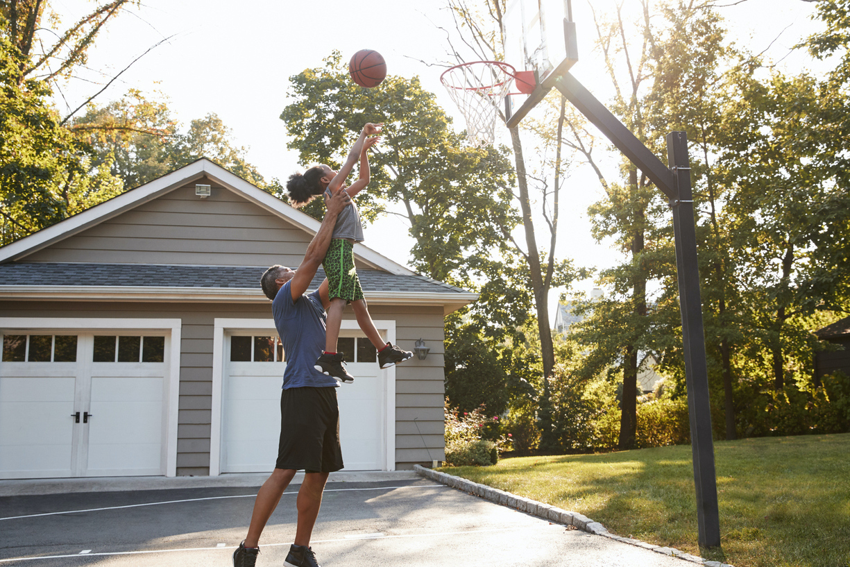 Father and son playing basketball in front front of Long Island, NY home.